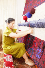 Smiling carpet weaver sideview