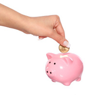 saving money, female hand is putting coin into piggy bank