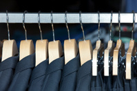 Men's suits on clothing rack.
