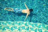 Man Swims Underwater in Blue Tile Swimming Pool