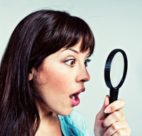 Look at that! amazed young woman looks through magnifying glass