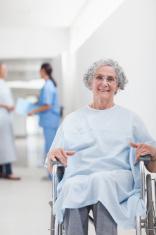 Elderly patient with wheelchair in corridor