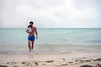 Modern Tattooed Tanned Father with Baby on White Sand Beach