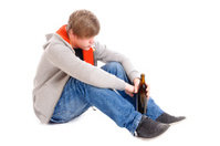Portrait of young drunk man sitting with bottle