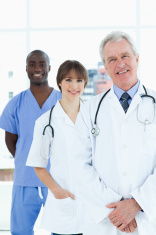 Medical intern standing upright behind his doctor and a colleagu