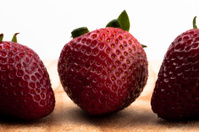 Three Strawberries on a Cutting Board