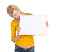 Angry student girl biting blank board
