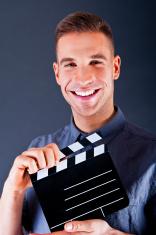 Man with movie clap over dark background