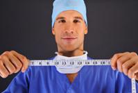 Surgeon with centimeter over dark background