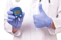 Doctor holding blood sugar meter. Showing OK sign