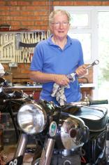 Senior Man Restoring Vintage Motorcycle In Garage