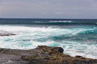 Turbulent ocean waves with white foam beat coastal stones