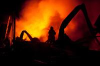 Silhouette of Firemen fighting a raging fire