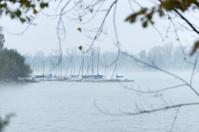 Foggy scene at an lake with sailing boats