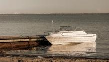 Motor boat parking aside rusty quay