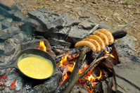 Fried eggs on fire at iron pan with grilled sausages