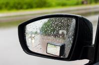 Wet by rain the car mirror, blurry roadway.