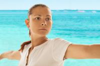 Woman doing yoga near ocean