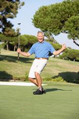 Senior Male Golfer On Golf Course Putting Green