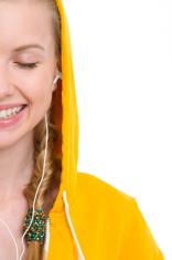 Closeup on happy teenager girl listening music in earphones
