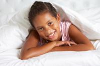 Young Girl Hiding Under Duvet In Bed