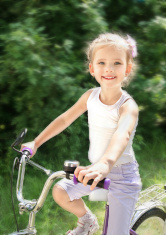 Smiling cute little girl with her bicycle