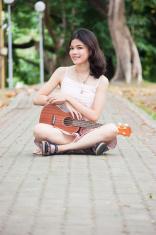 Asian girl with ukulele guitar outdoor