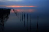 poles in the sea before sunrise
