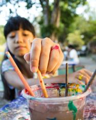 Asian girl picking paint brushes
