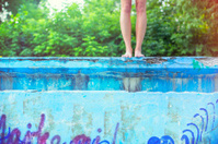 Young woman about to jump into empty old swimming pool
