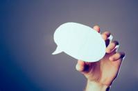 Hand holding a speech bubble