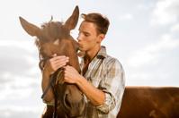 Young man kissing his horse.