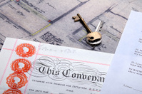 Property Mortgage deeds and house keys sit on top plans
