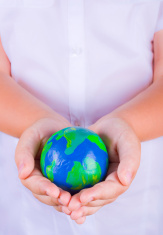 Child holding plasticine globe in hands
