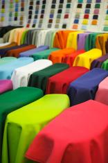 Rolls of multicoloured satin textiles.