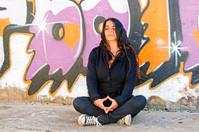 Young woman meditating at a graffiti brick wall