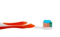 orange toothbrush and toothpaste on white