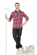 Young man standing with paint roller