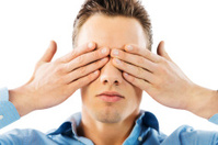 Young man covering his eyes.
