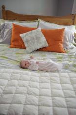 Newborn Girl Laying on Bed