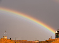 Wet red roofs and rainbow sky - golden evening light
