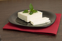 Sliced cheese on black dish with napkin