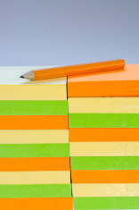 Stack of colorful sticky note pads with pencil