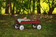 Preemie Newborn Boy Sleeping Peacefully in Red Wagon