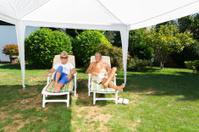 Senior couple resting in shade of garden tent