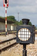 Old steel train sign lantern beside the railway's track.