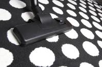 Vacuum cleaner on white dot carpet