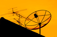 Satellite dish and home TV antenna in the evening