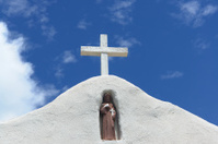 adobe church cross and statuette of saint francis