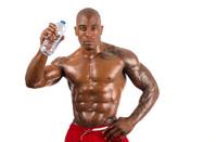 Black bodybuilder drinking water after a hard workout